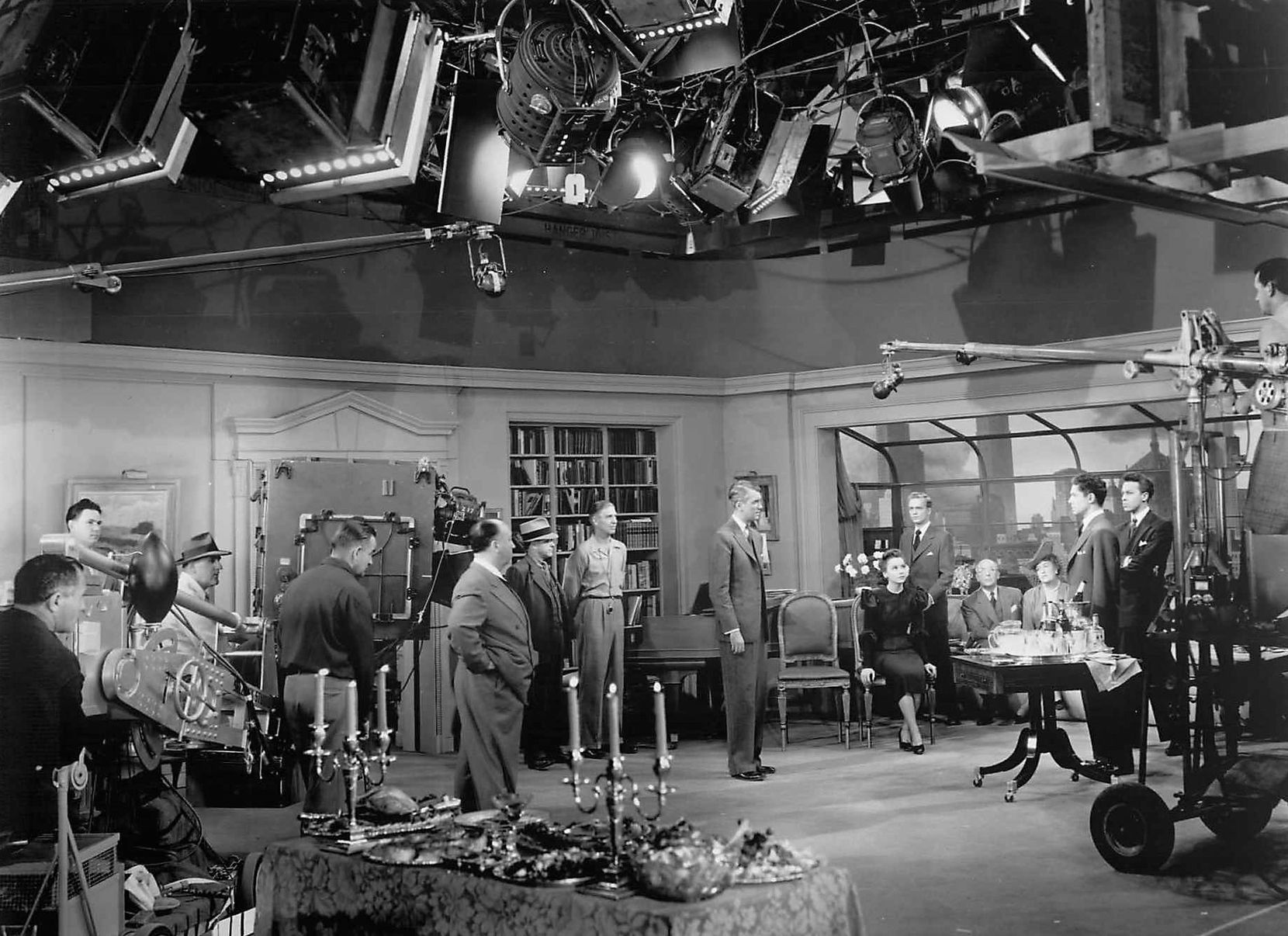 Director Alfred Hitchcock (center) rehearses star Jimmy Stewart and the cast as technicians look on during the making of Rope. Universal City Studios, 1948.