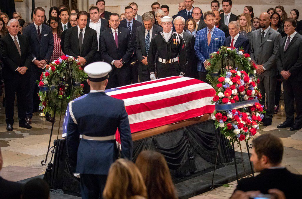 Sports figures, from left, Hale Irwin, Peyton Manning, Phil Mickelson, Mike Krzyzewski, Ken Raynor, Ben Crenshaw, Brad Faxon, Tim Finchem, Albert Pujols, and Tony La Russa, pay their respects at the flag-draped casket of President George H.W. Bush as he lies in the Rotunda of the U.S. Capitol on Tuesday, Dec. 4, 2018, in Washington.