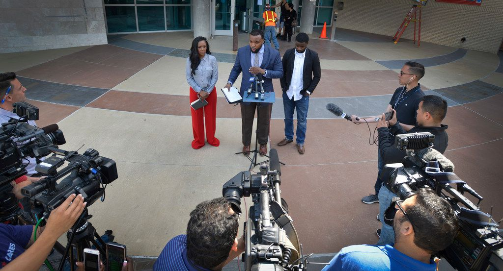 Dallas attorney Lee Merritt is flanked by K.C. Fox, left, a women's rights activist and minister Dominique Alexander during a press conference  outside the Dallas Police Department headquarters where Merritt outlined the accusations his client is making against R&B singer R. Kelly, which include giving her an STD.