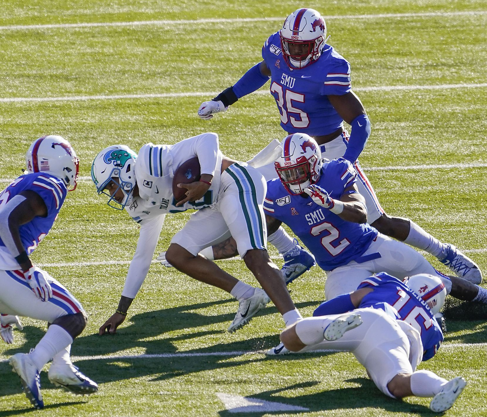 Tulane quarterback Justin McMillan (12) is brought down by SMU defensive end Delontae Scott (35), safety Patrick Nelson (2) and safety Trevor Denbow (16) during the first half of an NCAA football game at Ford Stadium on Saturday, Nov. 30, 2019, in Dallas.