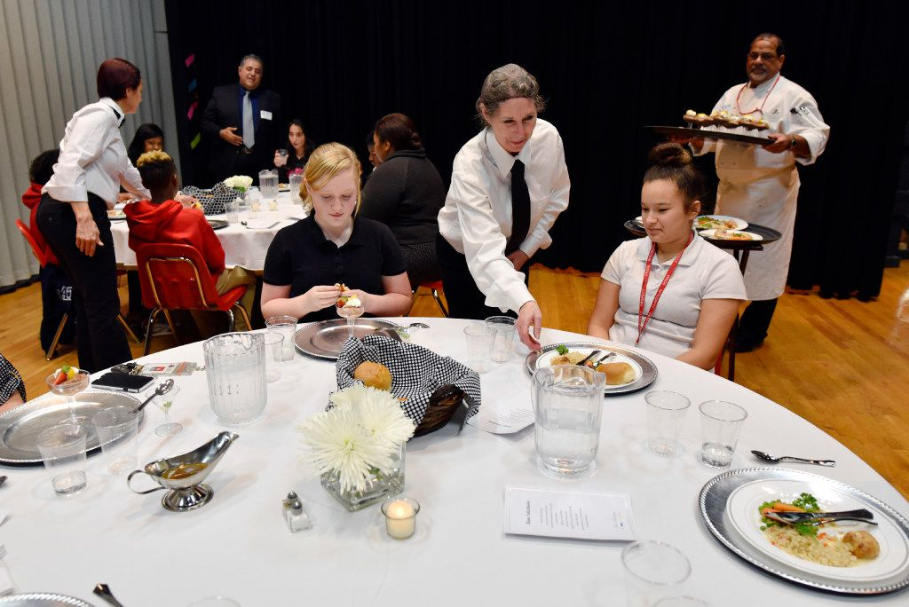 Dylan Holbert, 14, left, and Haley Alaniz, 13, are served their main dish from waitress Terry Young as students at Bessie Coleman Middle School in Cedar Hill ISD were treated to a five-course meal by food service company Sodexo  at Bessie Coleman Middle School in Cedar Hill.