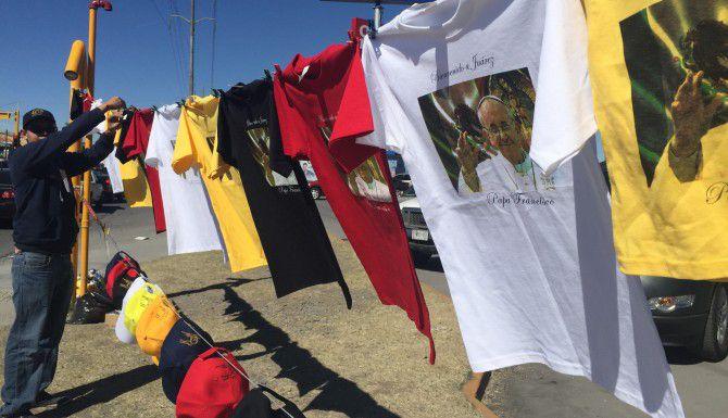 Gerardo Puga, de 25 años, vende camisetas, gorras, bufandas y llaveros con la imagen del Papa en una concurrida avenida de Ciudad Juárez.