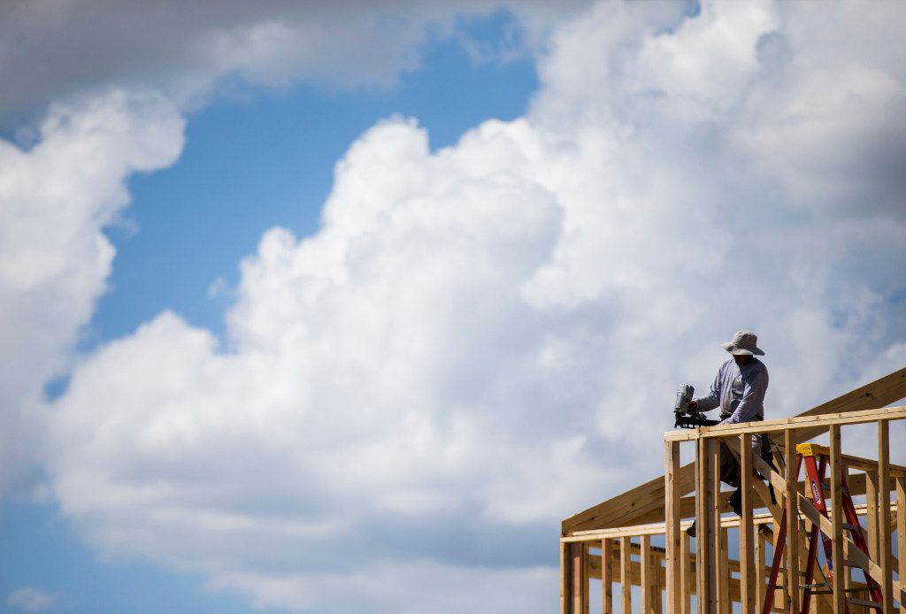 Construction workers frame new homes inside the Meritage Homes Villas at Las Colinas development on July 10, 2017.