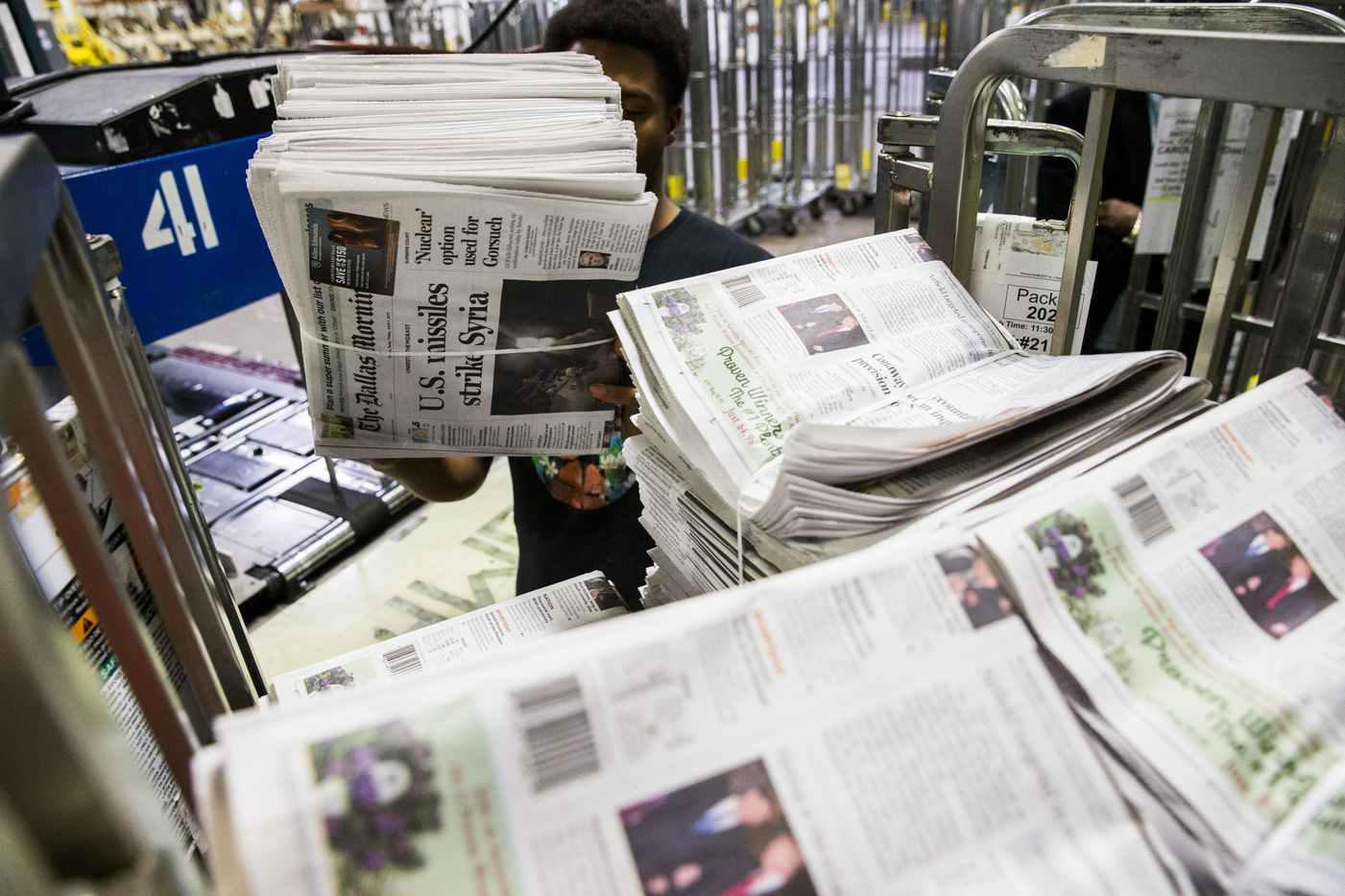An employee stacks copies of The Dallas Morning News' Friday, April 7, 2017 issue after they were printed. (Ashley Landis/The Dallas Morning News)