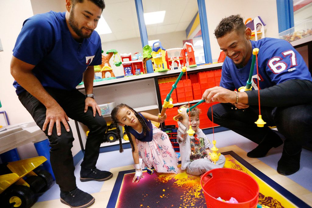 Texas Rangers'  Isiah Kiner-Falefa (left)  and Ronald Guzman (right) play a fishing game with Haleluya Shaga, 4, (left center) and Elliott Wyche, 3, during a visit to Medical City Children's Hospital in Dallas, Texas on Sept. 4, 2018.  (Nathan Hunsinger/The Dallas Morning News)