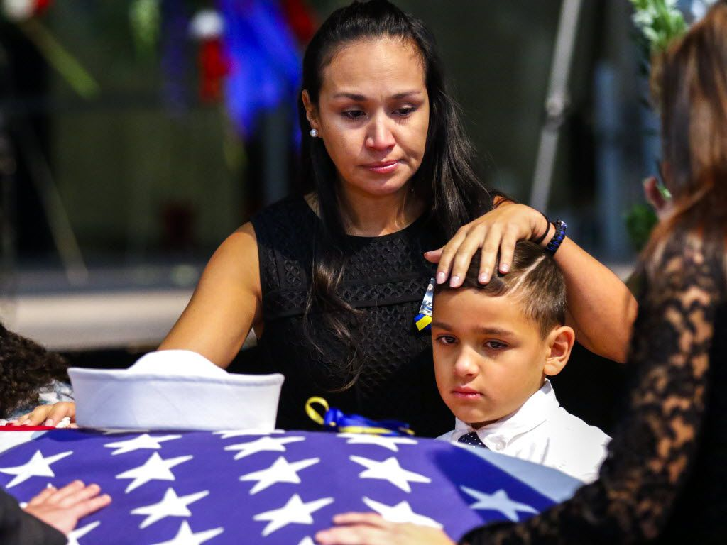 Kristy Villasenor (right) , partner of Dallas police officer Patrick Zamarripa, shares a moment with her son, Dylan, after a funeral service for Dallas police officer Patrick Zamarripa on Saturday, July 16, 2016 at Wilkerson-Greines Athletic Center in Fort Worth, Texas. Dylan is Patrick Zamarripa's stepson. Zamarripa was interred at DFW National Cemetery in Dallas, Texas. He was one of five officers killed by a gunman on July 7, 2016 during a Black Lives Matter rally in downtown Dallas, Texas. Zamarripa was a Navy veteran who served three tours in Iraq. He was 32. (Pool photo by Ashley Landis/The Dallas Morning News)