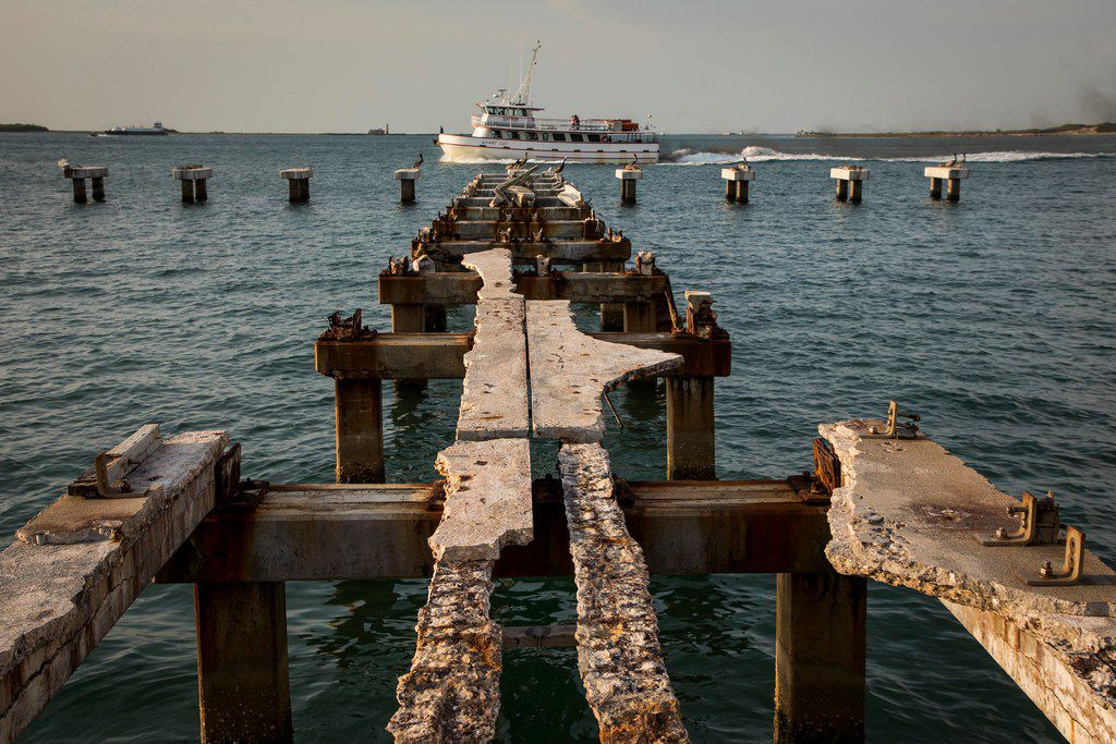The Wharf Cat charter fishing boat passes the remains of a pier destroyed by Hurricane Harvey as she returns to Fisherman's Wharf in Port Aransas on the Texas Gulf Coast.
