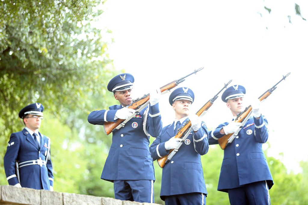 An Air Force honor guard perform a three-volley gun salute during the funeral honors for 10 veterans at Dallas' veterans cemetery.