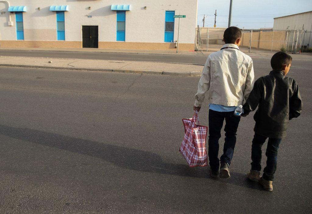 Carlos Joaquin Salinas, 27, of Santa Rosa, Guatamala, crosses the street with his son Fernando Salinas, 10, to a Tornado Bus station in El Paso on Saturday, March 30, 2019.