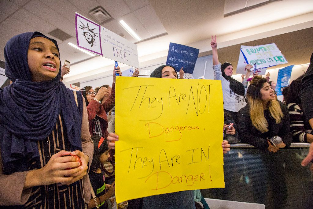 Protestors at DFW International Airport hold signs in opposition to President Donald Trump's executive order barring certain travelers on Sunday, Jan. 29, 2017.  (Smiley N. Pool/The Dallas Morning News)