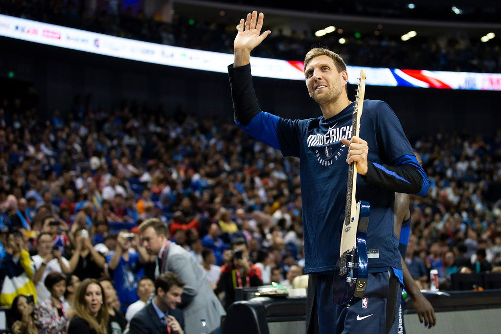 Dallas Mavericks forward Dirk Nowitzki waves to the crowd after being presented with a guitar by Chinese legend Wang Zhizhi during a timeout in the second half of an NBA China Games 2018 preseason basketball game against the Philadelphia 76ers at Mercedes-Benz Arena on Friday, Oct. 5, 2018, in Shanghai. (Smiley N. Pool/The Dallas Morning News)
