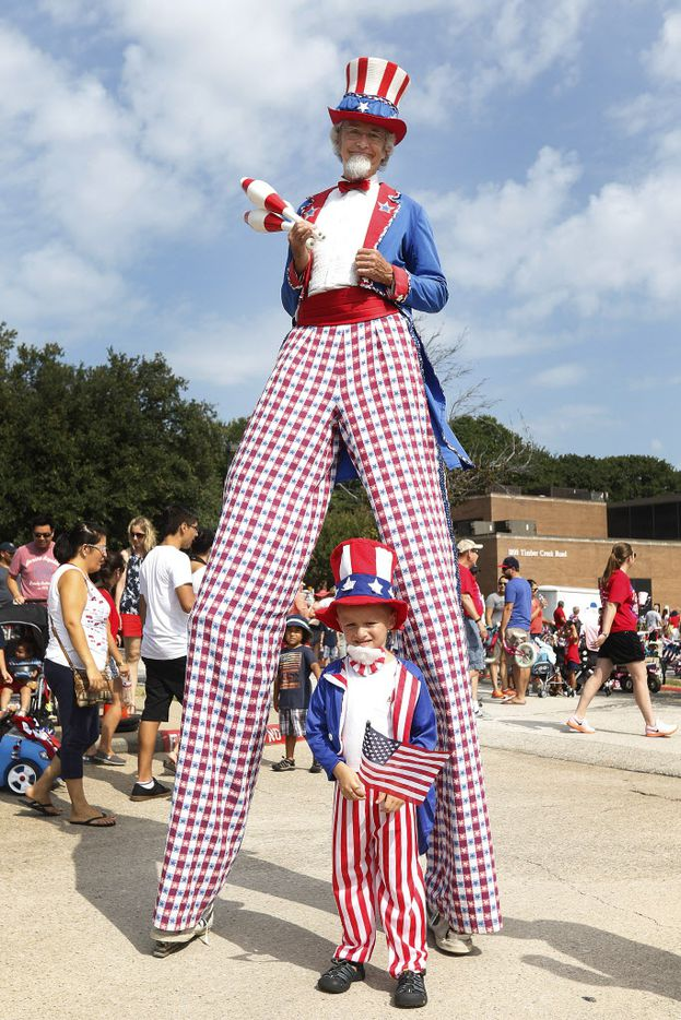 Dylan Laroche (bottom) poses for a photo with a man dressed as Uncle Sam on stilts during the Independence Fest Children's Parade in Flower Mound, Texas on Saturday, July, 4, 2015.
