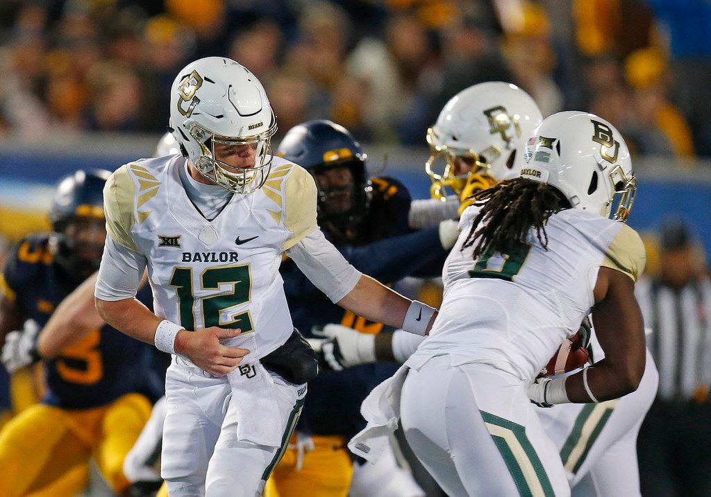 MORGANTOWN, WV - OCTOBER 25:  Charlie Brewer #12 of the Baylor Bears hands off to JaMycal Hasty #6 against the West Virginia Mountaineers at Mountaineer Field on October 25, 2018 in Morgantown, West Virginia.  (Photo by Justin K. Aller/Getty Images)