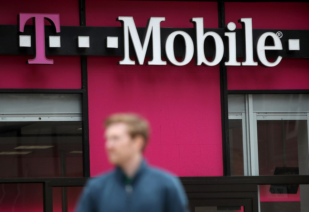 A pedestrian walks by a T-Mobile store in San Francisco. T-Mobile and Sprint Corp. agreed to combine in a $26.5 billion merger.