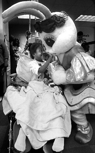 1993: Five-year-old Sharifa Bouldin of Dallas  gets a hug from one of the Lisa Frank Ballerina Bunnies who visited sick children at Children's Medical Center. The animated characters appeared in the Adolphus/Children's Christmas Parade.