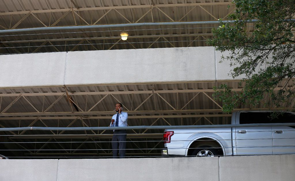 A man talks on his cell phone inside the parking garage next to an office building in Lake Highlands where police found two people dead inside the office in Dallas, Monday, April 24, 2017. (Jae S. Lee/The Dallas Morning News)