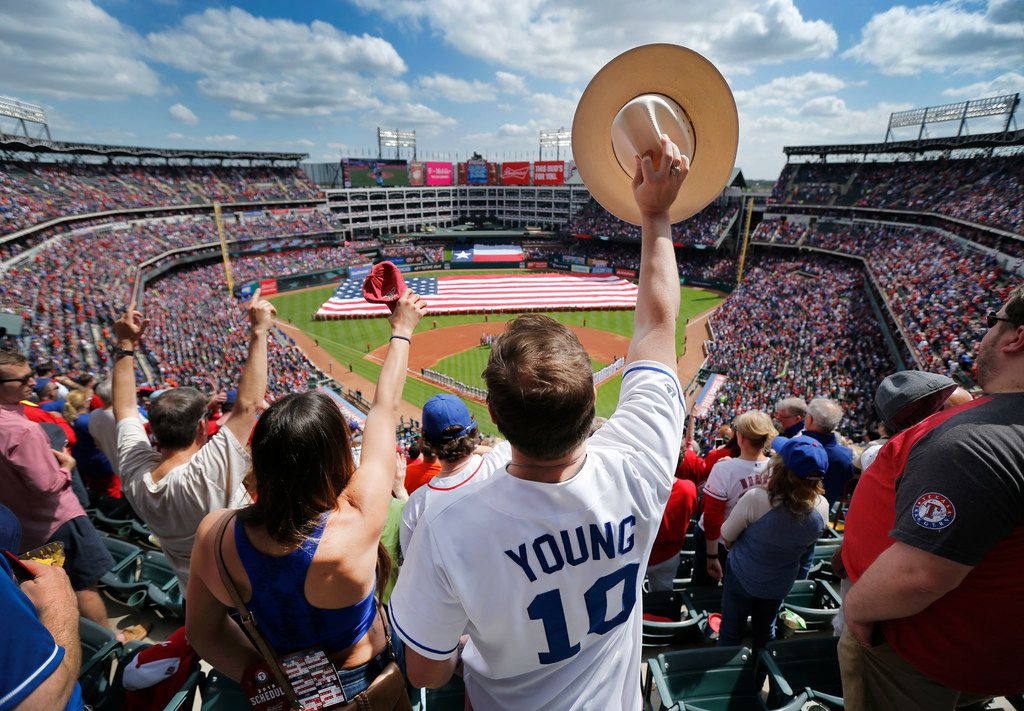 Texas Rangers and Michael Young fan Andrew Brown and his wife Andrea of Plano cheer after the playing of the national anthem during Opening Day festivities at Globe Life Park in Arlington, Texas, Thursday, March 29, 2018. (Tom Fox/The Dallas Morning News)