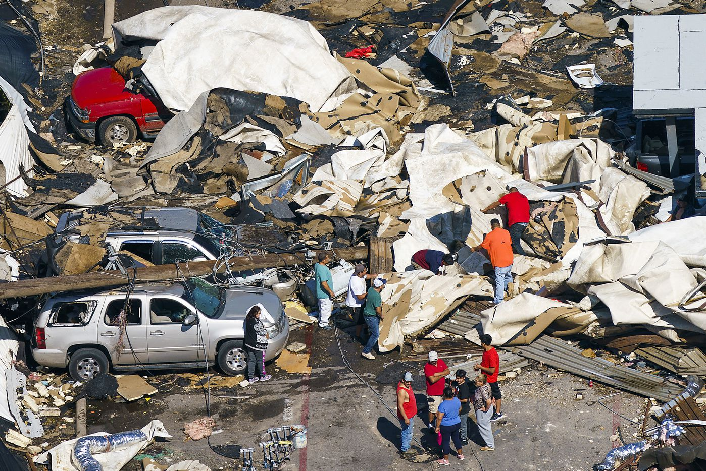 People pick through the rubble left by a tornado near Walnut HIll Lane and Denton Drive on Monday, Oct. 21, 2019, in Dallas.