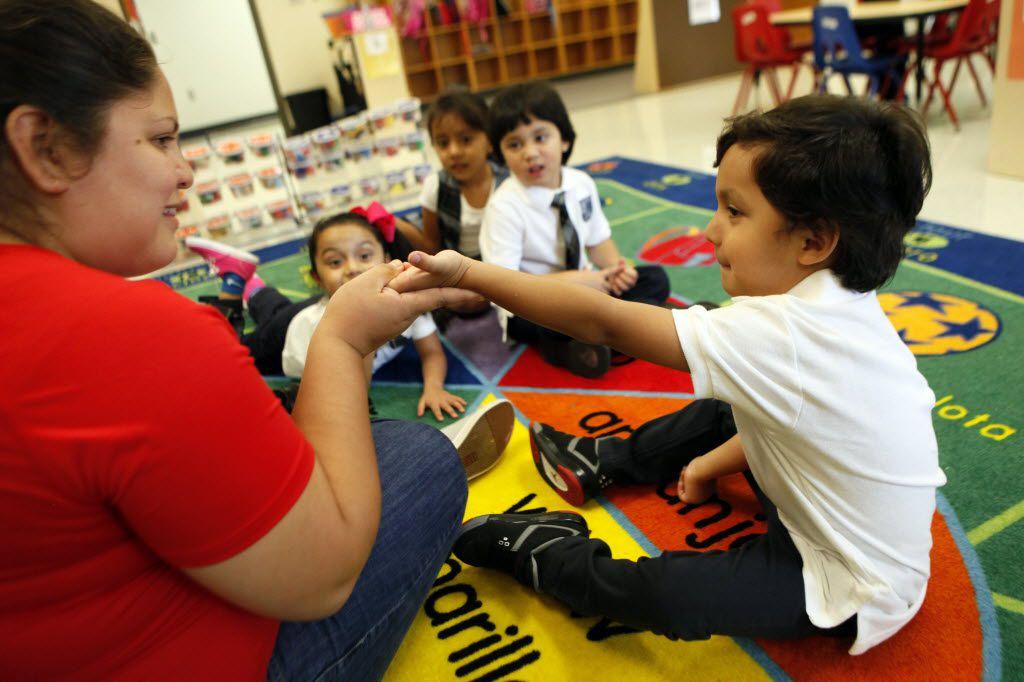 "Pre-K bilingual teacher Elizabeth Villalta holds the hand of 3-year-old Nicholas Jaramillo as she reads to the class the Spanish children's book ""Un Beso en Mi Mano"" at Leonides Gonzalez Cigarroa MD Elementary School."