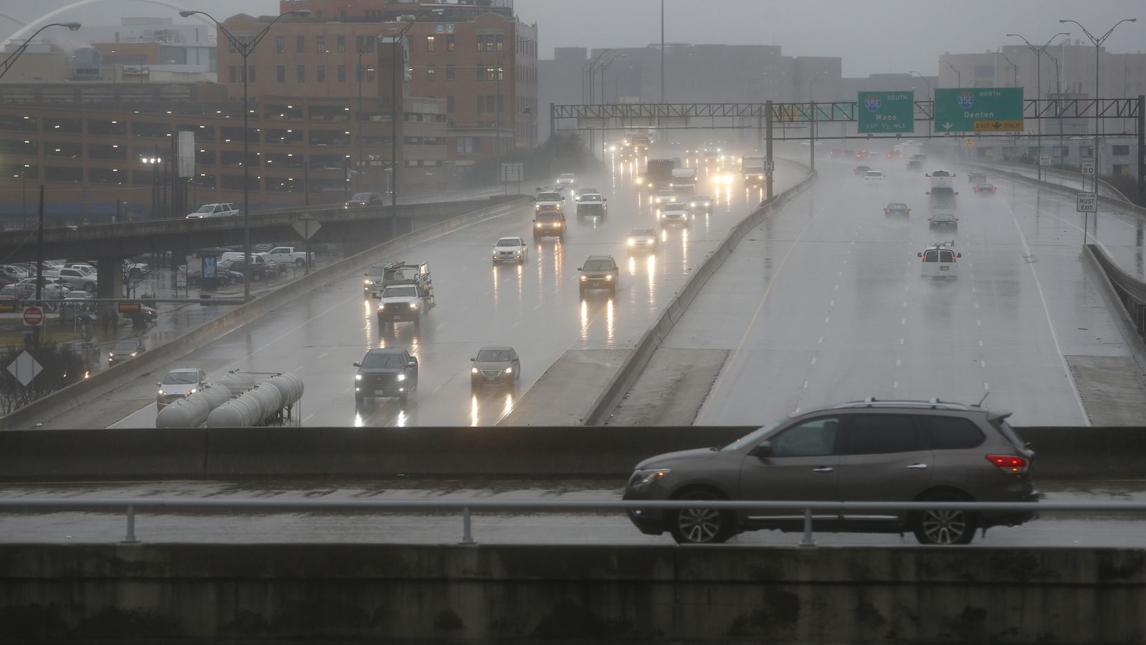 A car passes on St. Paul Street over Woodall Rodgers Freeway on a cold, rainy morning in Dallas on Jan. 2, 2019.