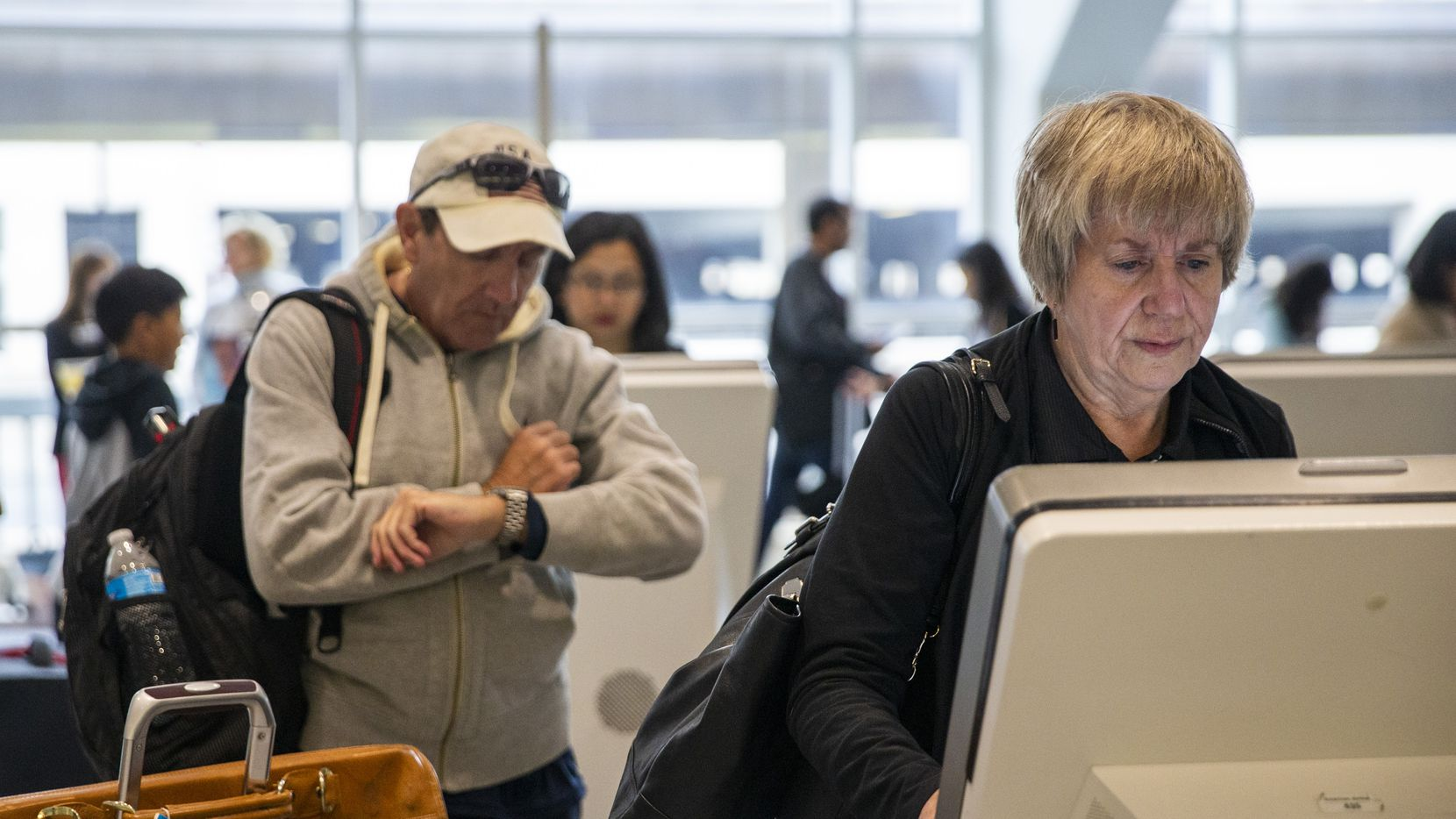 Kelcie Hibbs (right), from Fort Worth, Texas, utilizes an American Airlines electronic kiosk in the ticketing area of Terminal A at DFW International Airport in Irving, Texas, on Friday, November 22, 2019. American Airlines is making major changes to its apps and websites, including a system that lets customers make their own bids when a flight is overcrowded. (Lynda M. Gonzalez/The Dallas Morning News)