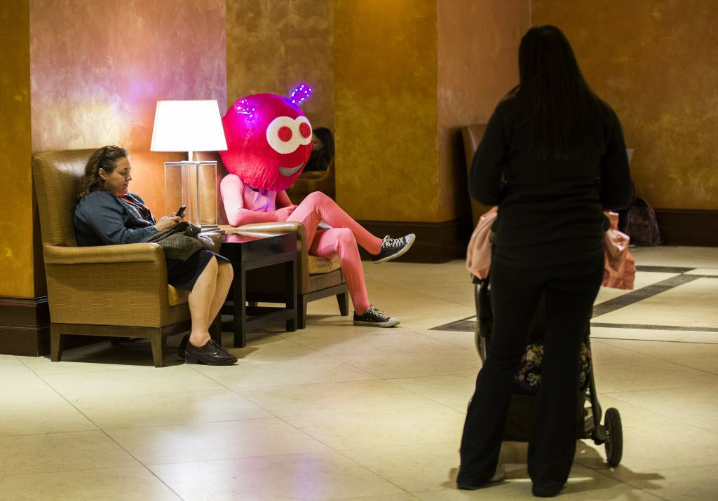 A street performer takes a break to check his email with other SXSW attendees in the lobby of the Hilton hotel during the 2015 SXSW interactive and film festival on Sunday, March 15 in down tow Austin.