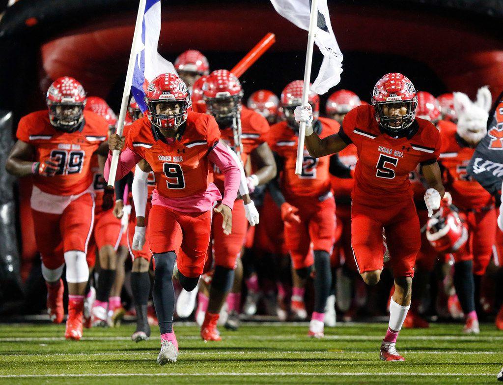 Cedar Hill High's Kirk Lockhart (9) and T'Mar White (5) lead their team onto the field to face Mansfield Lake Ridge High at Longhorn Stadium in Cedar Hill, Texas, Friday, October 19, 2018. (Tom Fox/The Dallas Morning News
