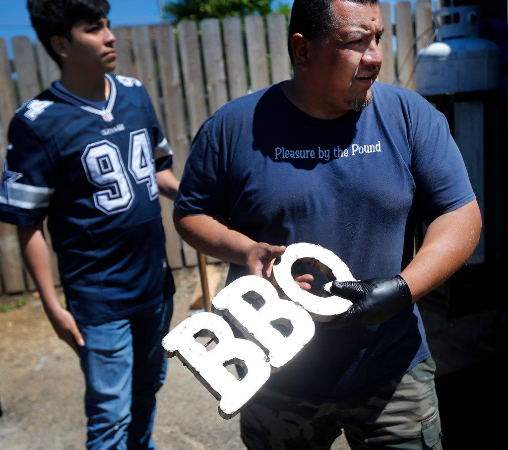 Panther City BBQ co-pitmaster Chris Magallanes (right) puts out the BBQ sign as they turn out lunch from their trailer adjacent to The Republic Street Bar on Hattie St. in Fort Worth, Saturday, April 19, 2019. (Tom Fox/The Dallas Morning News)