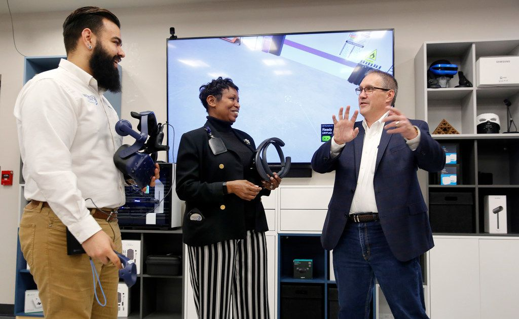 Frank St. John, executive vice president of Lockheed's Missiles and Fire Control division (right), visits with electrical engineer A.J. Tate (left) and tech strategy and innovation lead Jan Alexander as they demonstrate virtual and augmented realities in the company's Innovation Center Genesis Lab in Grand Prairie.