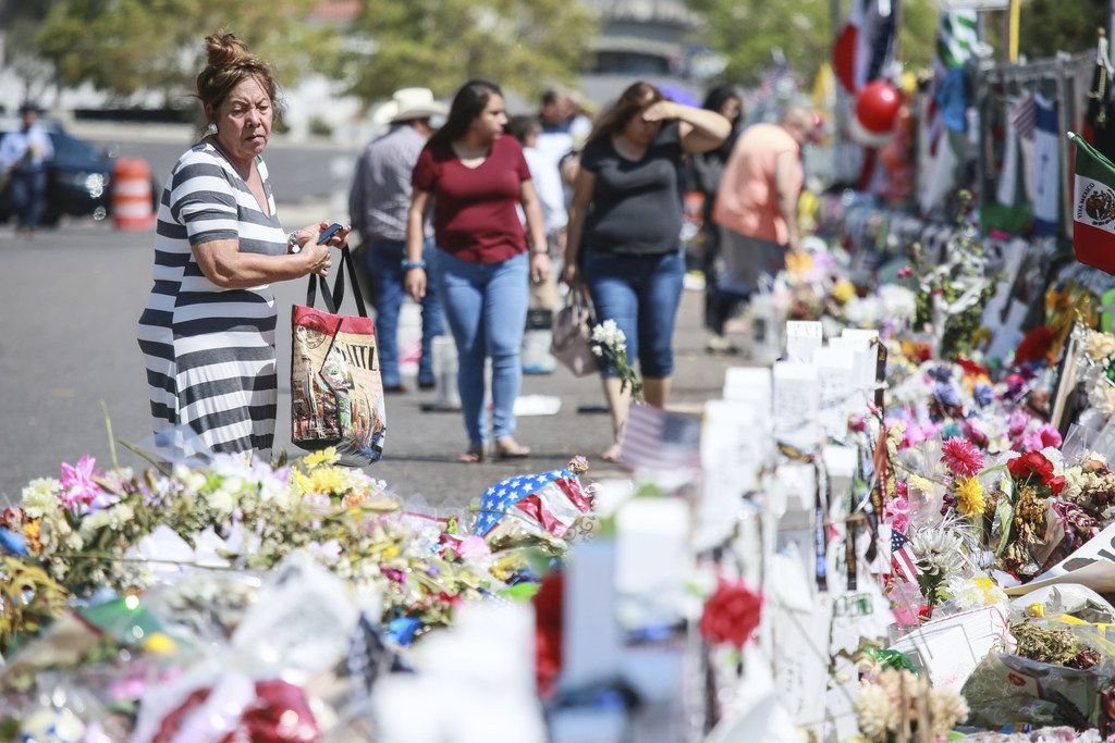 People gather at a makeshift memorial honoring victims outside Walmart in El Paso, Texas.