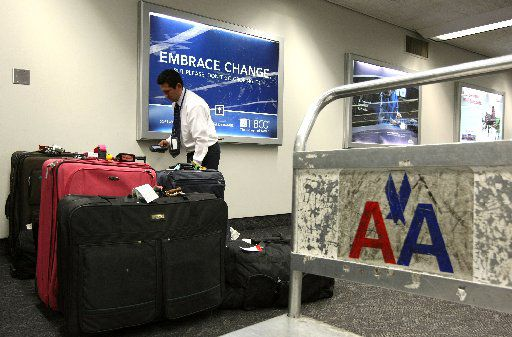 ORG XMIT: *S0423291884* SAN FRANCISCO - MAY 21:  An American Airlines employee scans baggage May 21, 2008 at San Francisco International Airport in San Francisco, California. American Airlines announced today that it plans  to charge $15 for the first checked bag on all flights beginning in mid-June in an effort to recoup money lost due to the rising fuel costs. The airline also announced it will cut some flights and staff.  (Photo by Justin Sullivan/Getty Images) 81186297