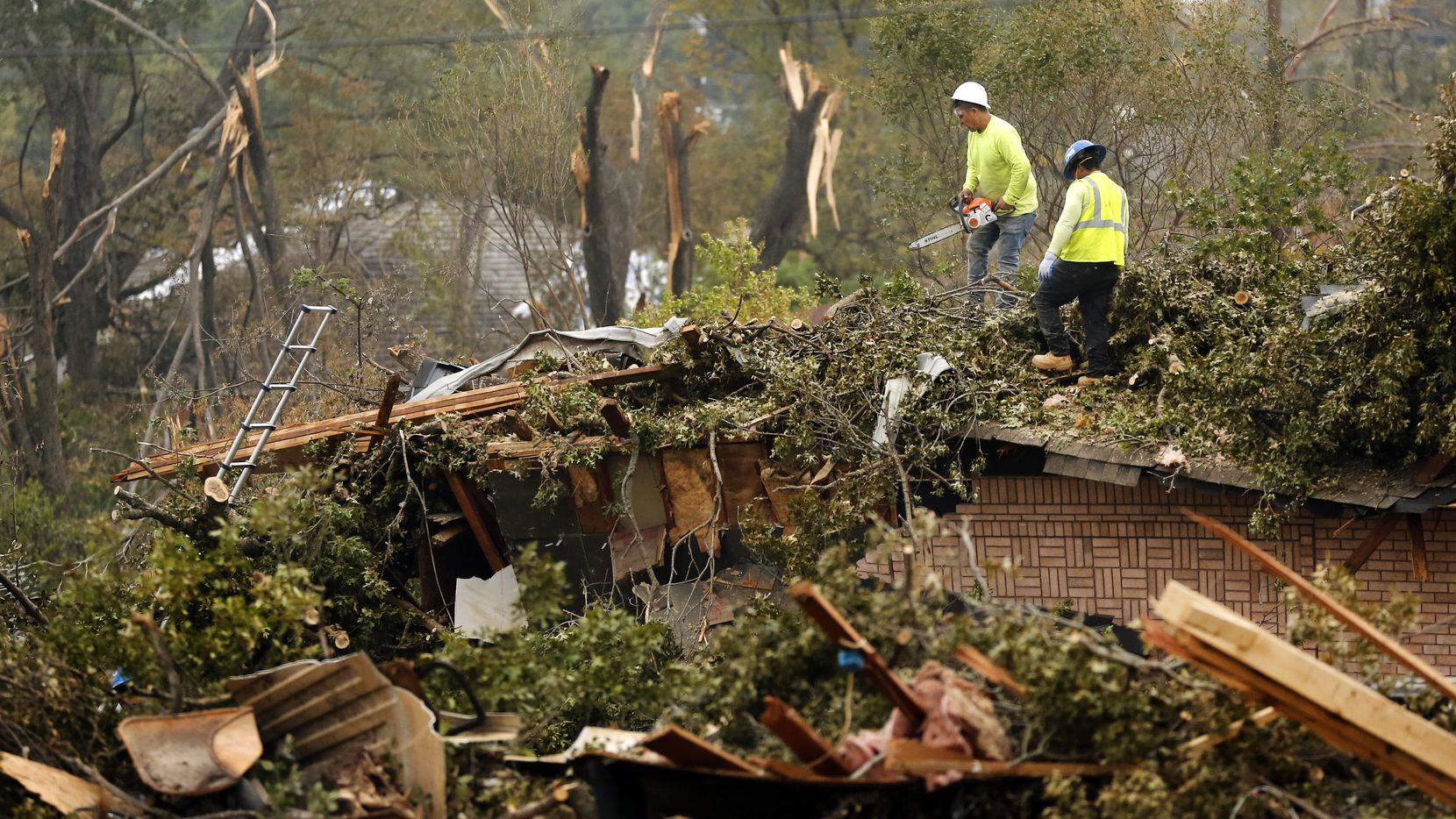 Crewman cut up and remove a tree that toppled onto a home on Royal Lane in northwest Dallas.