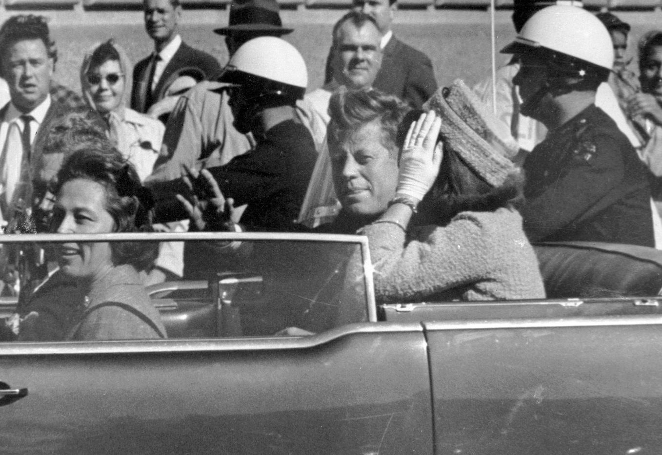 Approximately one minute before he was shot, Pres. John F. Kennedy waves from his car as the motorcade passed through downtown Dallas. Riding with Kennedy are First Lady Jacqueline Kennedy (right), Texas first lady Nellie Connally (left), and her husband, Texas Gov. John Connally.