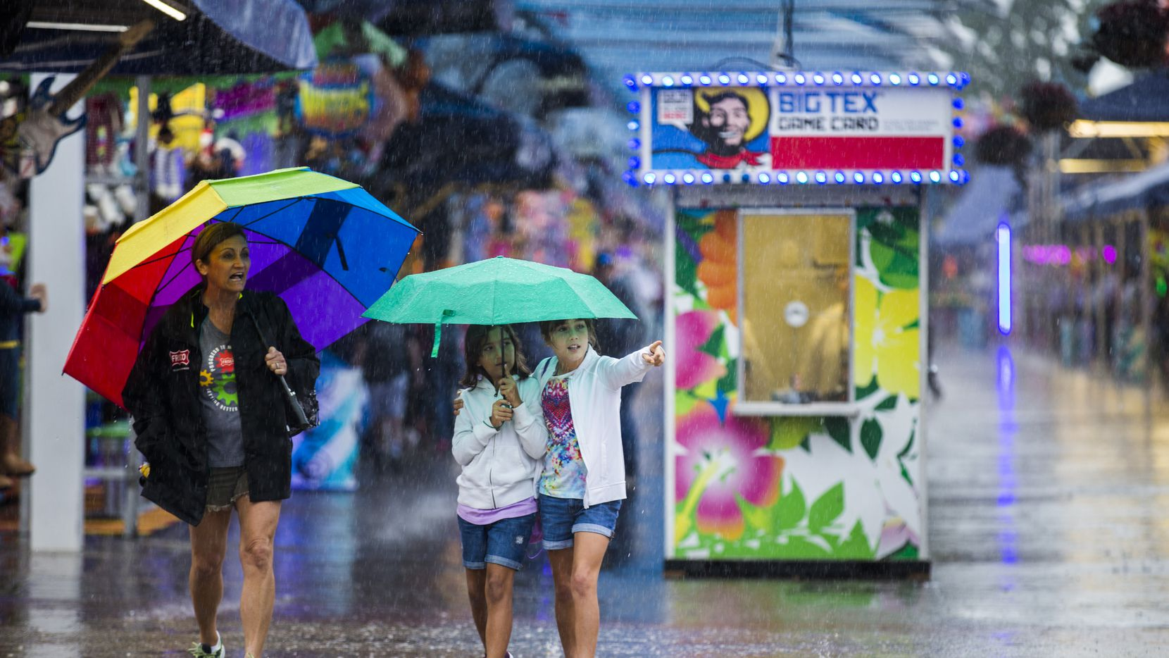 Julie Fernandez, Catalina Fernandez, 10, and Kariss Fernandez, 10, walked through the midway in the rain at the State Fair of Texas on Tuesday.