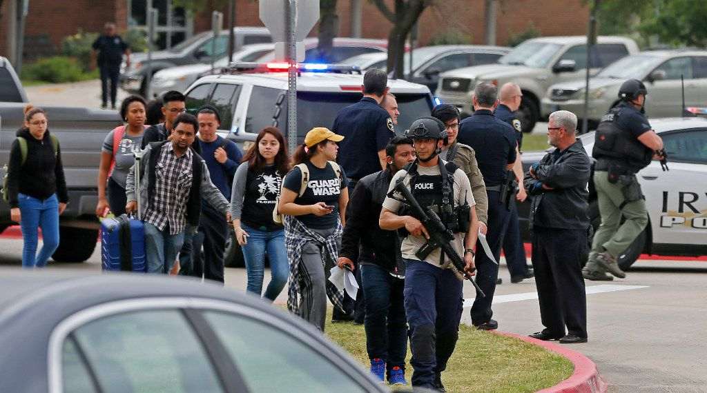 An officer leads a group of students walking out of the building as Irving police officers work at a fatal shooting scene on the North Lake College campus in Irving on Wednesday.