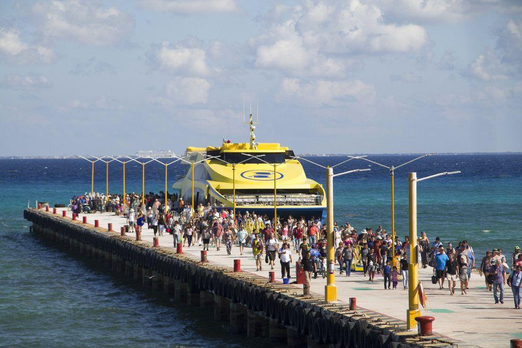 Turistas y pasajeros desembarcan de un ferry a un embarcadero en Playa del Carmen, México, el viernes 2 de marzo de 2018. (AP Foto/Gabriel Alcocer)