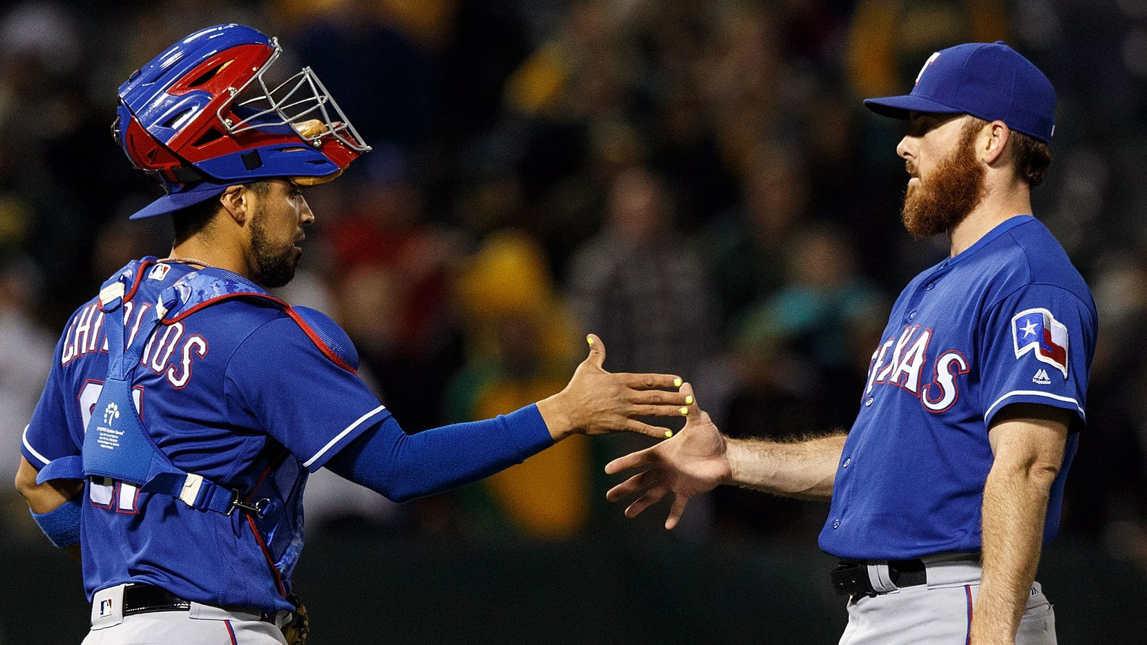 OAKLAND, CA - JUNE 14:  Robinson Chirinos #61 of the Texas Rangers celebrates with Sam Dyson #47 after the game against the Oakland Athletics at the Oakland Coliseum on June 14, 2016 in Oakland, California. The Texas Rangers defeated the Oakland Athletics 10-6. (Photo by Jason O. Watson/Getty Images)