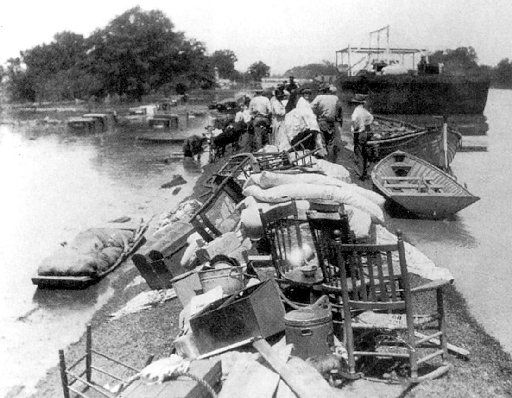 With the Mississippi River on one side and the flood on  the other, the levee itself provided the only high ground. Here  refugees piled everything they could save onto the crest of a  levee.