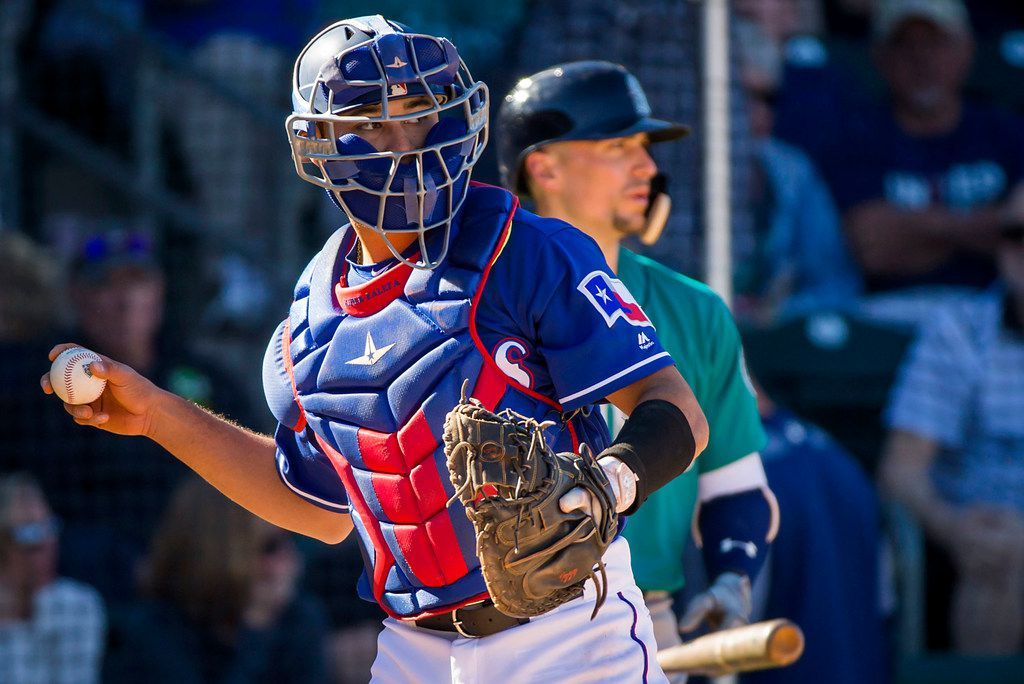 Texas Rangers catcher Isiah Kiner-Falefa makes a throw back to the pitcher during the seventh inning of a spring training baseball game against the Seattle Mariners on Sunday, March 4, 2018, in Surprise, Ariz. (Smiley N. Pool/The Dallas Morning News)