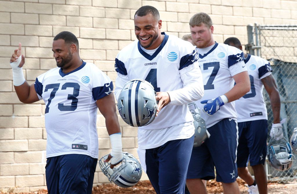Dallas Cowboys quarterback Dak Prescott (4) laughs as he makes his way onto the field in front of Dallas Cowboys offensive guard Joe Looney (73) before the afternoon practice at training camp in Oxnard, California on Monday, July 24, 2017. (Vernon Bryant/The Dallas Morning News)