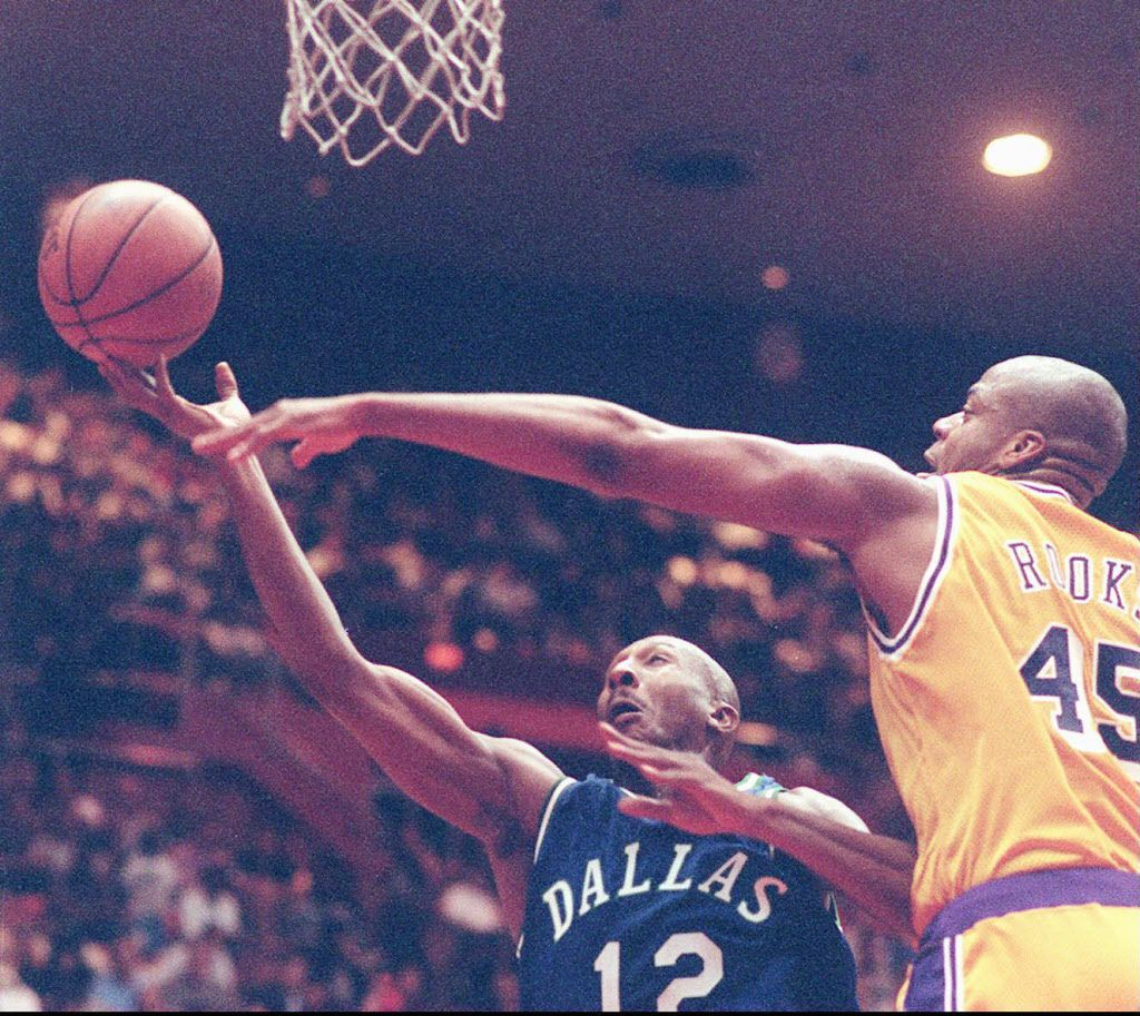 Los Angeles Lakers' Sean Rooks ( right) and Dallas Mavericks' Derek Harper struggle for a ball  during an exhibition game between the Los Angeles Lakers and the  Dallas Mavericks Wednesday, Oct. 16, 1996, in Fresno, Calif. The Lakers won 90-80 (AP Photo/Thor Swift)
