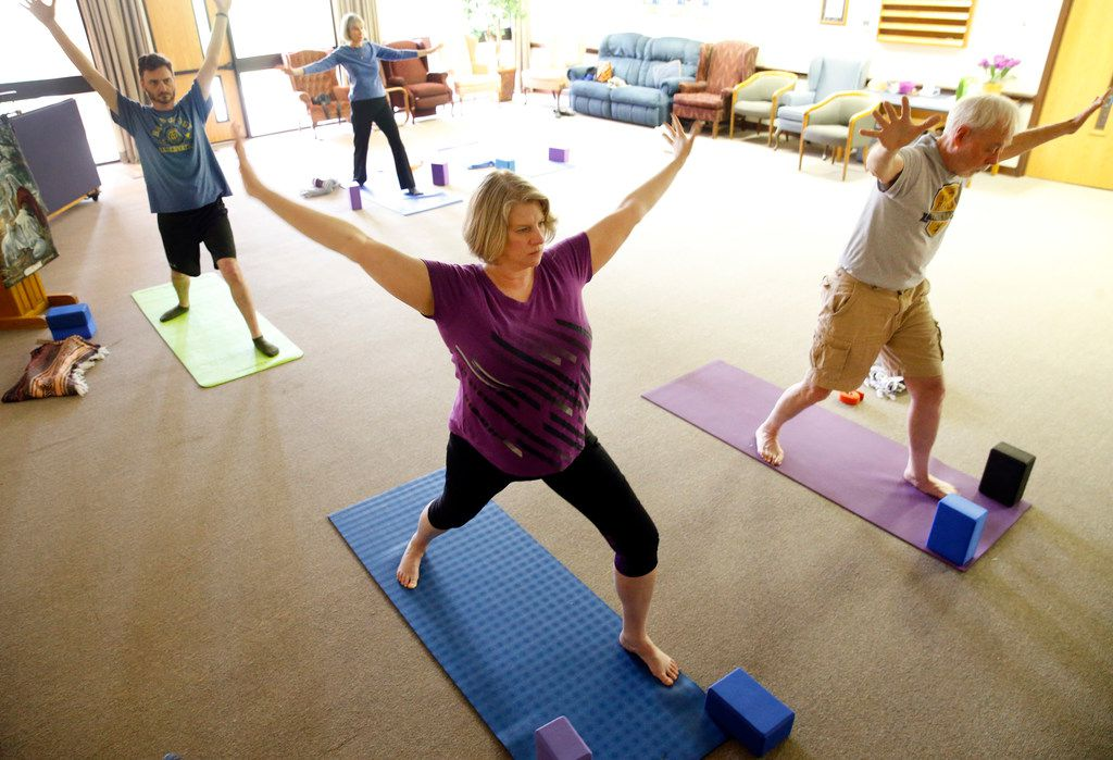 Senior pastor Valarie Englert (in purple) and congregation members Tom Hilbun (back) of Garland, Ann McMann of Garland and David Barton participate in a yoga class held at the First United Methodist Church in Garland.