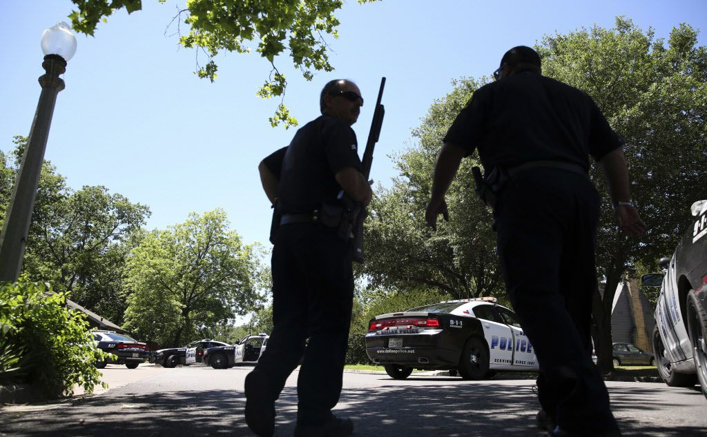 Dallas Police walk a neighborhood a block away from a shooting in Dallas, Monday, May 1, 2017. Authorities said a Dallas paramedic has been shot while responding to a shooting call. (AP Photo/LM Otero)