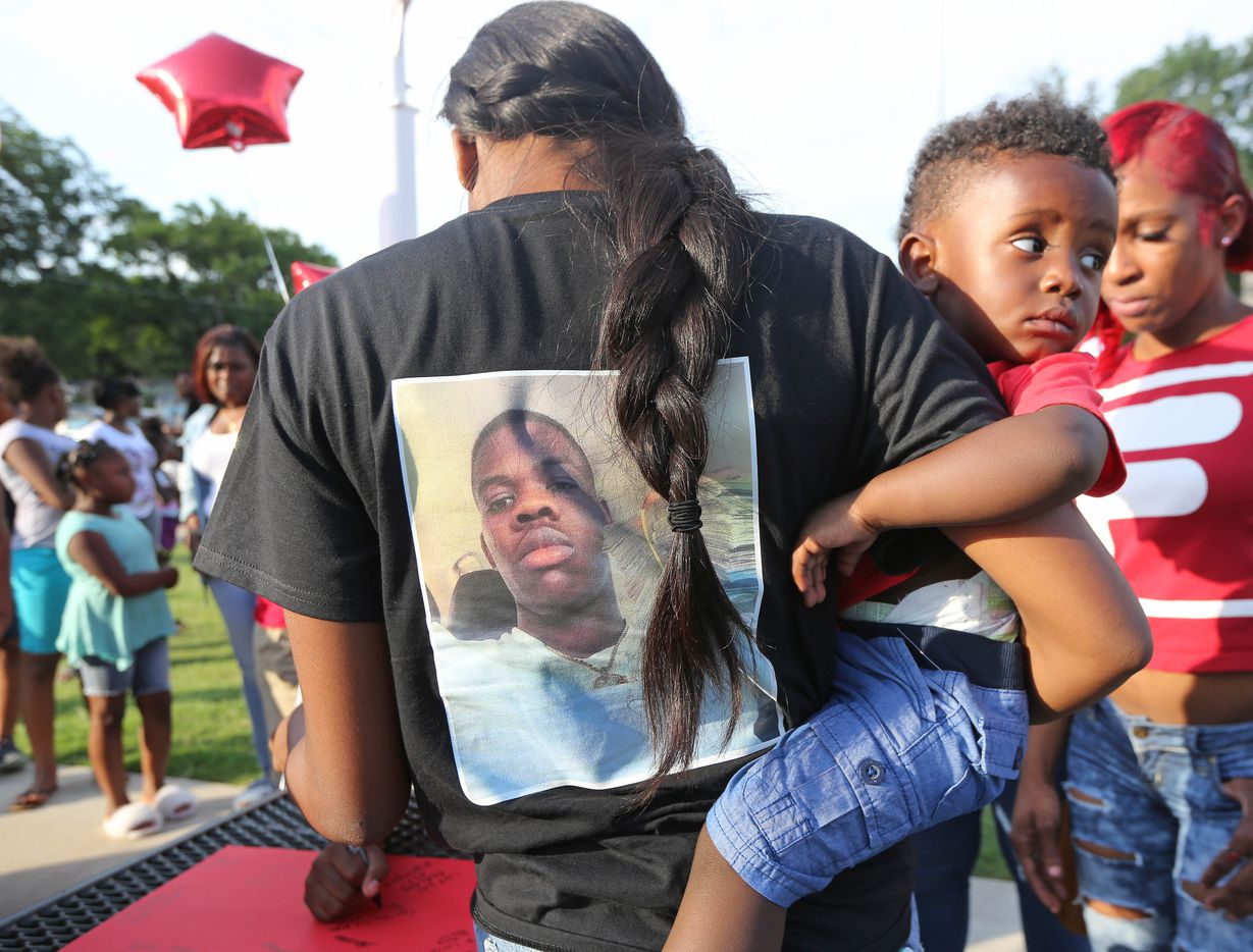 Terrinique Bowens holds her son King as she wears a T-shirt honoring slain youth Mike Titus at the vigil in Cummings Park.