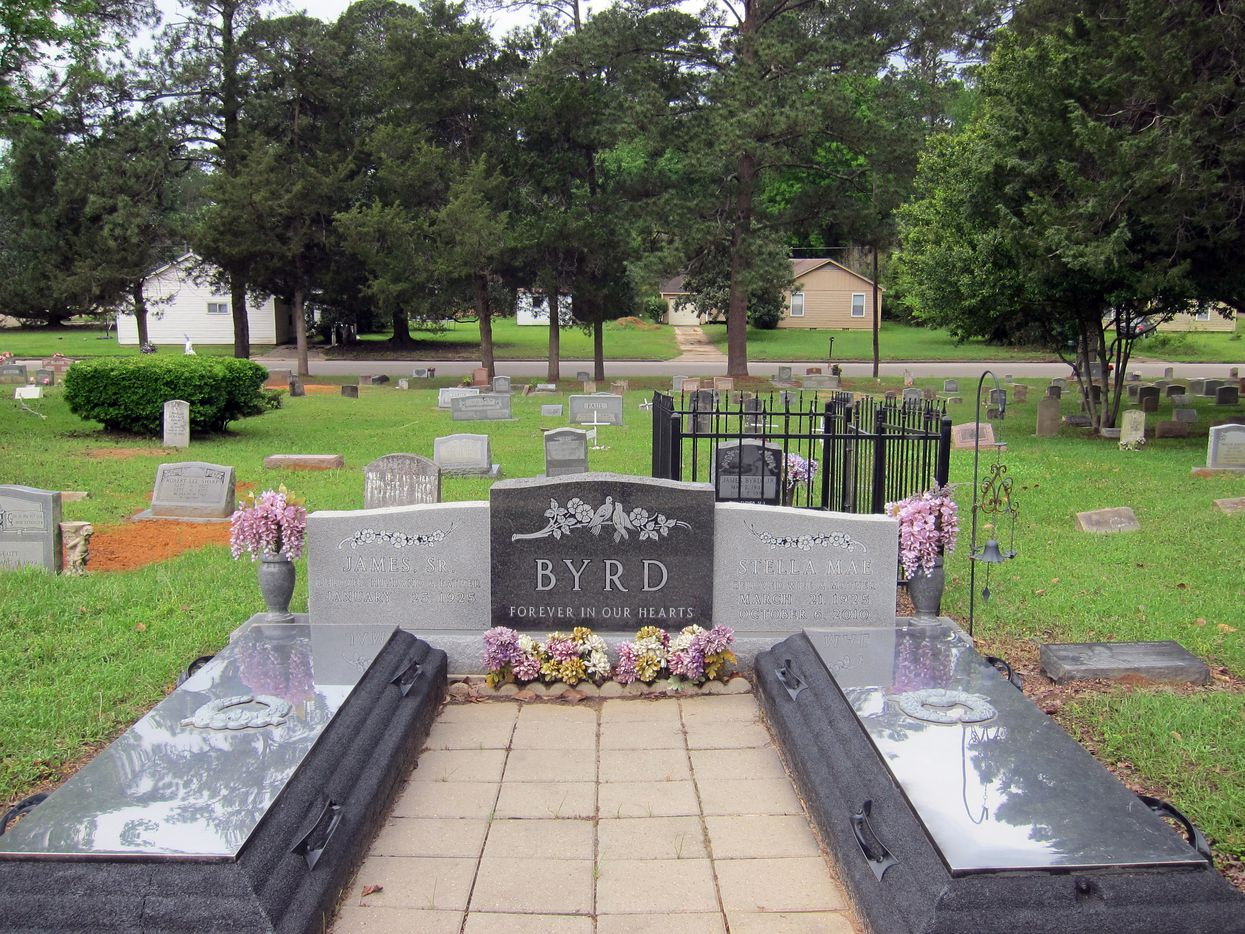 This Friday, April 12, 2019 photo shows the gravesite of James Byrd Jr. in Jasper, Texas. Byrd was killed on June 7, 1998, after he was chained to the back of a pickup truck and dragged for nearly three miles along a secluded road in the piney woods outside Jasper in what is considered one of the most gruesome hate crime murders in recent Texas history. In front of Byrd's gravesite, which was surrounded by a fence after being twice desecrated, sit the burial plots for his mother and father. Byrd's mother, Stella, died in 2010, while his father, James Sr., is still alive and resides in Jasper. (AP Photo/Juan Lozano)