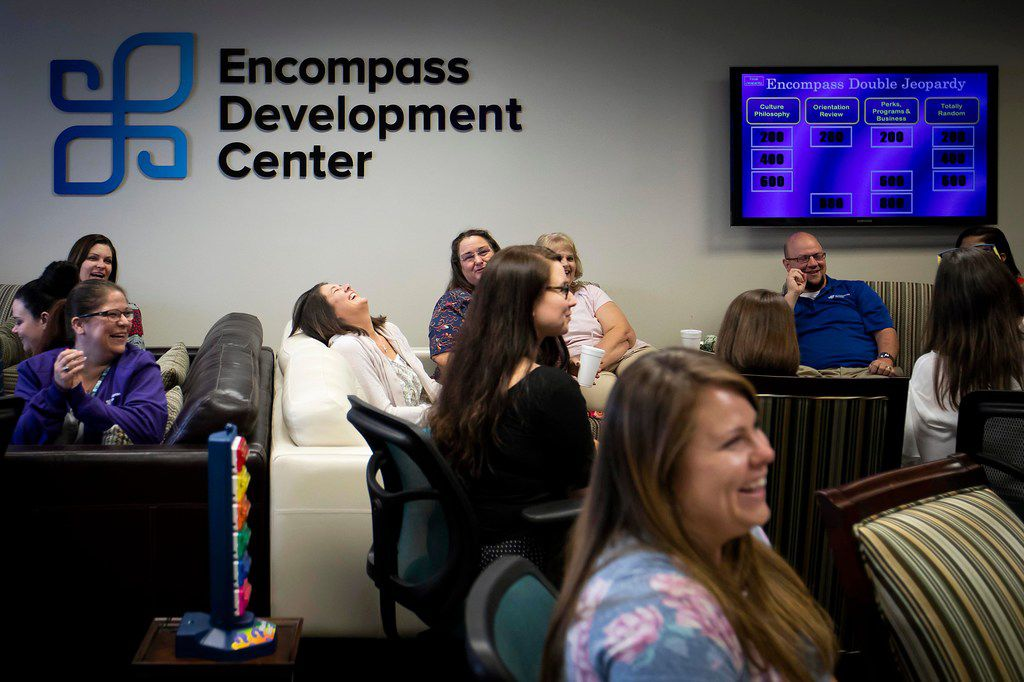 """Encompass Home Health and Hospice employees laugh while playing a game of """"Encompass Jeopardy"""" during a class at the Encompass Development Center."""