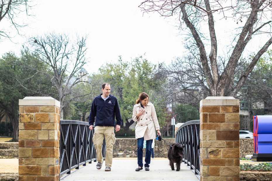 "Ken Bohacs, left, and Alyssa Bohacs, both of Dallas, walk with their dog Max at Williams Park in Dallas, near the ""LOVE"" statue."