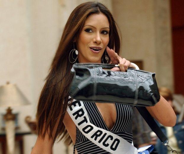 Alba Reyes, Miss Puerto Rico, señala durante su llegada al hotel en Quito, Ecuador, jueves 27 de mayo, 2004. (AP Photo/Dolores Ochoa)