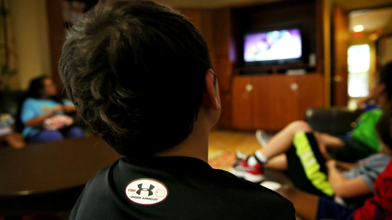 A boy watches TV at Jonathan's Place, which serves abused and neglected children, in Garland.