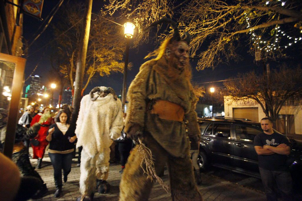 Krampus characters walk passed businesses along Main Street during the Dallas Krampus Walk through the streets of Deep Ellum, organized by the Krampus Society and Dark Hour Haunted House, on Friday, Dec. 5, 2014.